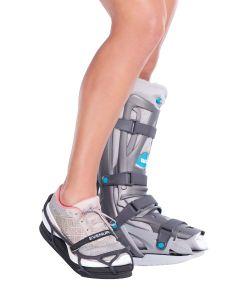 Im Vordergrund das linke Bein mit einem Schuh und einer Ausgleichsohle. Im Hintergrund das rechte Bein mit dem VACOped.